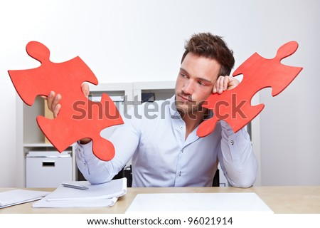 Pensive business man with two oversized red jigsaw puzzle pieces in office
