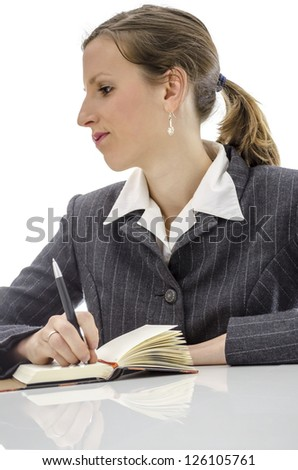 Pensive business woman thinking what to write in her diary. Isolated over white background.