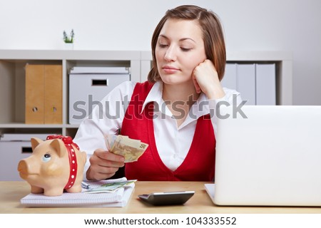 Pensive business woman with Euro money and piggy bank in office