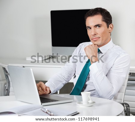 Pensive businessman working with laptop at his desk in the office