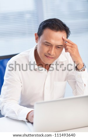Pensive businessman working with laptop at the table