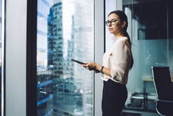 Pensive businesswoman dressed in formal apparel standing near panoramic window in enterprise company and thinking about trade investment,thoughtful female entrepreneur in eyewear for vision protection