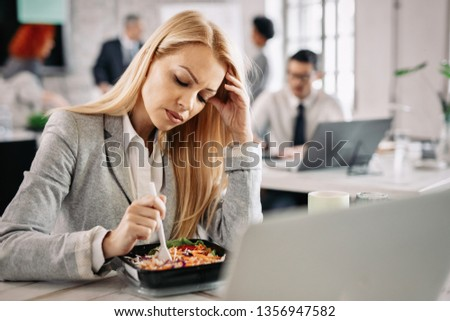 Pensive businesswoman eating vegetable salad during her lunch break in the office.
