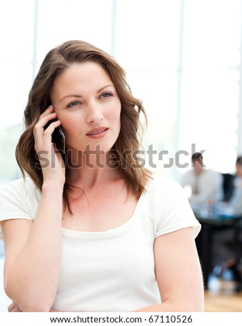 Pensive businesswoman on the phone while her team is working in the background