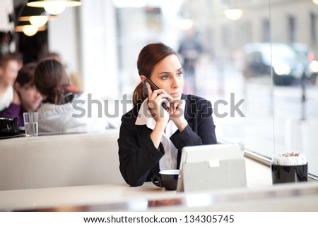 Pensive businesswoman talking on the phone in a cafe - stock photo