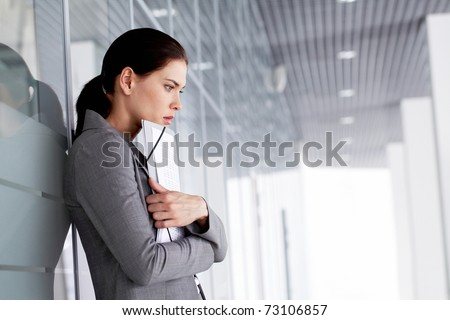 Pensive businesswoman with documents by wall