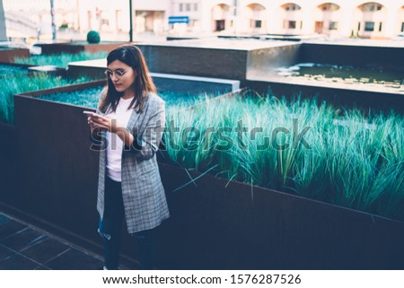 Pensive caucasian woman in trendy wear standing on urban setting browse on smartphone and read income messages,female blogger share publication and using app on cellular connected to 4G internet