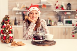 Pensive child enjoying chritmas and tasty cookies on kitchen table and christmastree. Cheerful happy adorable teenager girl in home kitchen with delicious biscuits and xmas tree in the background