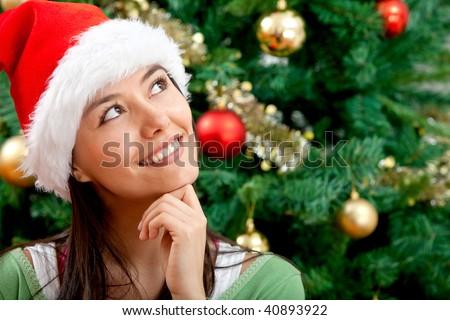 Pensive Christmas woman portrait with a Santa hat