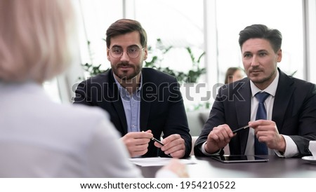 Pensive confident businessmen talk speak with business partner or client at meeting in office. Successful young Caucasian male employers have interview with job candidate. HR, employment concept. Foto stock ©
