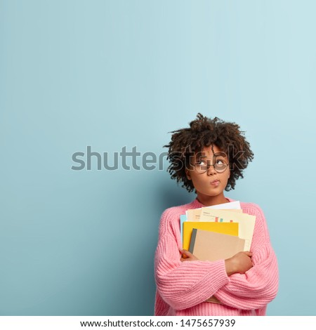 Pensive dark skinned college student holds papers and textbooks, purses lips and focused upwards, wears rosy knitted sweater, stands against blue background with copy space for your advertisement