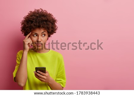 Pensive dark skinned woman keeps finger on temple, looks aside thoughtfully, uses new gadget for first time, dressed casually, tries to remember name of product before browsing internet, has idea