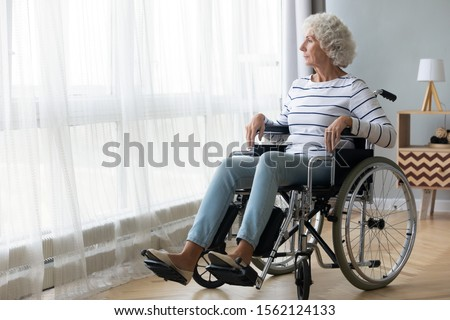 Pensive disabled senior grandma patient sit on wheelchair alone at home hospital look through window, thoughtful sad old woman feel depressed lonely, retired people disability and loneliness concept