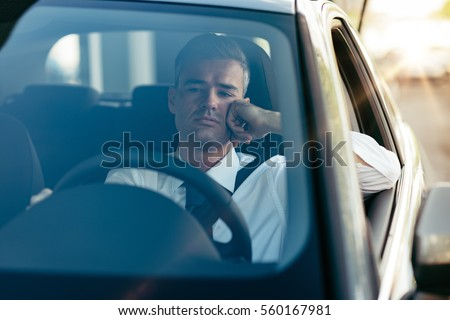 Pensive disappointed businessman sitting in his car and thinking with hand on chin