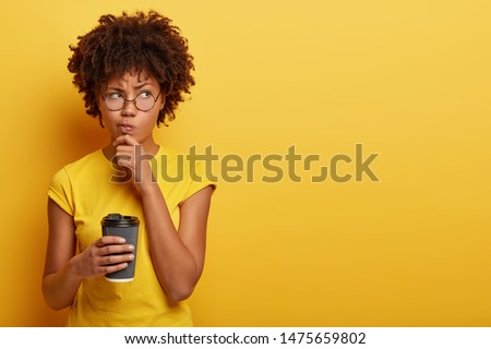 Pensive displeased woman with dark skin, holds chin and looks away, contemplates about something, wears yellow t shirt, holds disposable cup of coffee, smirks face and being upset by bad thoughts