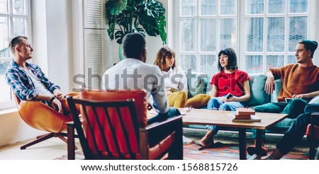 Pensive diverse business partners in casual clothes sitting at table in soft armchairs and on couch and discussing startup project at home. Meeting in coworking office