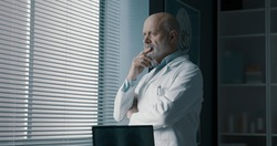Pensive doctor standing next to a window in his office and looking away, healthcare professionals concept