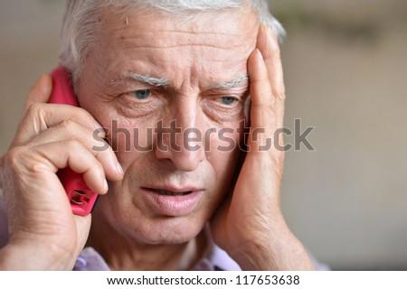 pensive elderly man calling on the phone