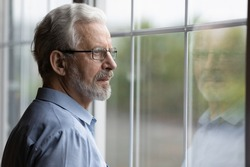 Pensive elderly mature senior man in eyeglasses looking in distance out of window, thinking of personal problems. Lost in thoughts elderly middle aged grandfather suffering from loneliness, copy space