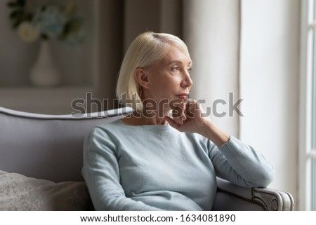 Pensive elderly woman sit on couch look in window distance thinking remembering past good days, thoughtful middle-aged senior female feel distressed lost in thoughts pondering or planning