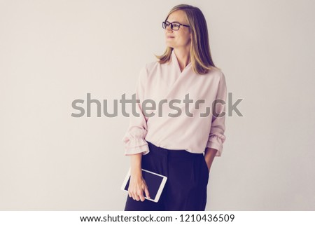 Pensive enterprising businesswoman thinking of new project. Smiling introspective confident female business executive holding tablet and looking away. Aspirations concept