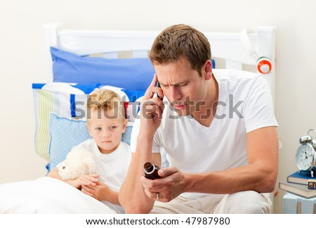 Pensive father giving cough syrup to his sick son sitting on bed