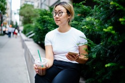 Pensive female blogger dressed in white t shirt with copy space area for brandname holding takeaway beverage and smartphone technology and thinking on idea for web content, concept of communication