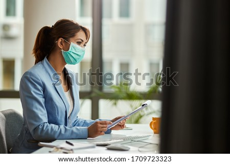 Pensive female entrepreneur with face mask working on business reports in the office. Copy space.