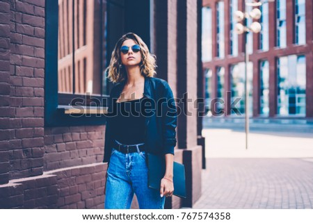 Pensive female in sunglasses walking on city street passing buildings facades enjoying free time, beautiful hipster girl dressed in casual wear strolling on urban background with publicity area #767574358