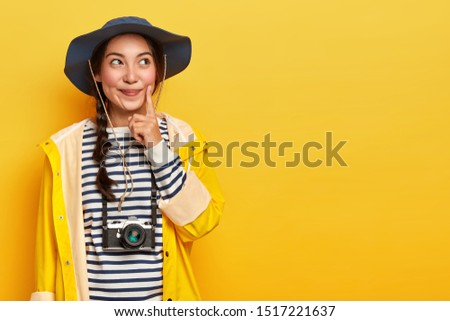 Pensive female tourist keeps index finger on cheek, thinks what way to choose, explores local surrounding during hiking trip, wears retro camera on neck, headgear and yellow waterproof raincoat
