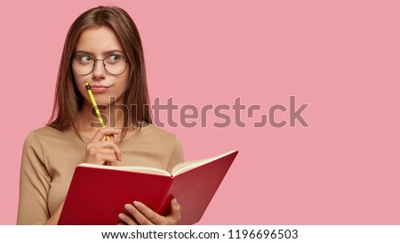Pensive female writer ponders on new ideas, holds red notebook and pencil near mouth, has thoughtful expression, wears big round glasses, isolated over pink background with copy space on right