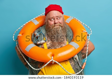 Pensive fisherman has thick beard poses with fishing net inflated lifebuoy looks away thinks about sea cruise angling during spare time isolated over blue background. Thoughtful seafarer with lifering Stok fotoğraf ©