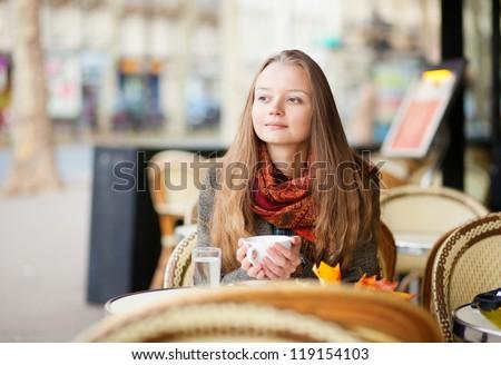 Pensive girl in a Parisian outdoor cafe