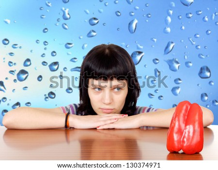 Pensive girl looking a red pepper with a wet blue background (focus in the pepper)