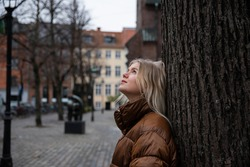 Pensive girl looks up and observes the sky. She wears a brown vest, it's winter and it's cold. Worried concept