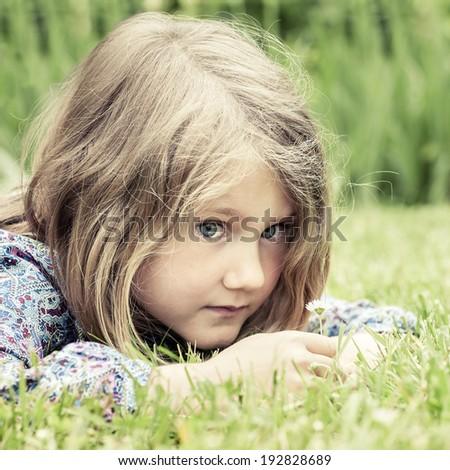 Pensive girl lying on grass