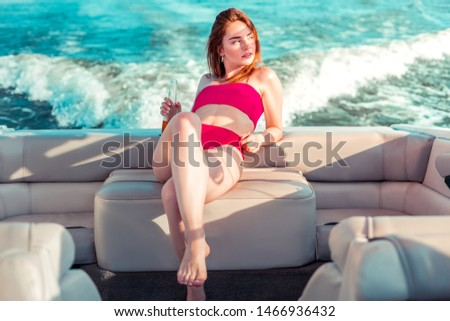 Pensive girl. Thoughtful young pretty girl in a red swimming suit with a bottle in her hand sitting in a pleasure boat