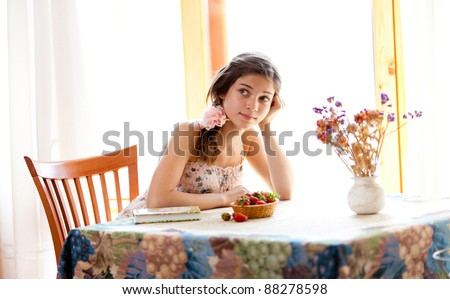 Pensive girl with book sitting at table indoor in summer day with strawberries