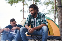 Pensive guy enjoying outdoor recreation while roasted marshmallows over the fire with his friends. Stock photo