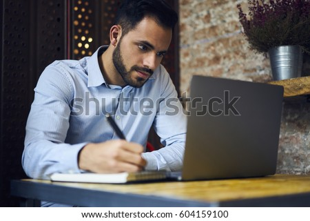 Pensive handsome bearded male owner of trading company searching information about marketing agency noting their contacts to arrange formal meeting sitting in coworking space with laptop computer