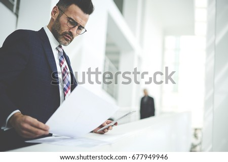 Pensive handsome matured male owner of corporation reading financial documentation standing near copy space for advertising, confident businessman in trendy formal wear checking accounting report  Stockfoto ©