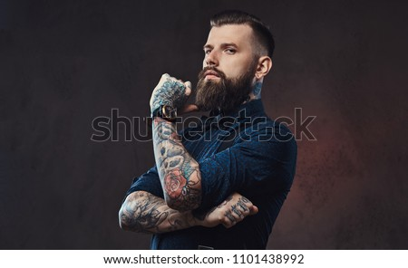 Pensive handsome old-fashioned hipster in a blue shirt and suspenders, standing with hand on chin in a studio. #1101438992