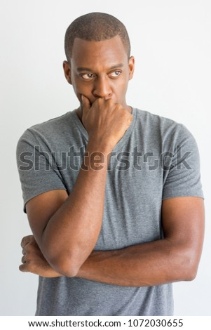 Pensive handsome young African man leaning on hand while thinking. Serious introspective guy in t-shirt focusing on problem. Reflecting concept