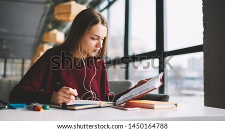 Pensive hipster girl learning language online via earphones using application while writing new words into textbook, attractive smart woman enjoying playlist music at cafeteria and studying