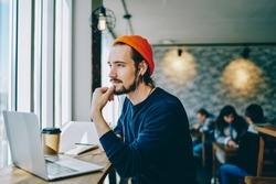 Pensive hipster guy in earphone looking away listening music via app on laptop computer, dreamy male caucasian student enjoying audiobook thinking on ideas for blog publication in coworking space