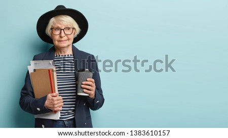 Pensive intelligent female professor holds takeaway coffee, notepad with papers, has break after conducting lectures, wears black headgear, formal coat, models over blue studio wall. Retired woman