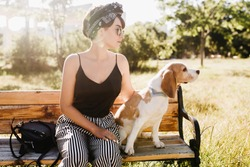 Pensive lady wears black ribbon in hair looking away while sitting on wooden bench with beagle dog. Outdoor portrait of serious lady in sunglasses with pet on blur nature background.