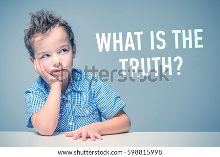 Pensive little boy in a blue shirt sitting at the table next to the inscription 'What is the truth?' #598815998