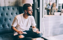 Pensive male in casual clothes and eyeglasses writing poetry enjoying music through wireless earphones and drinking coffee while sitting on couch in cafe and looking away out the window