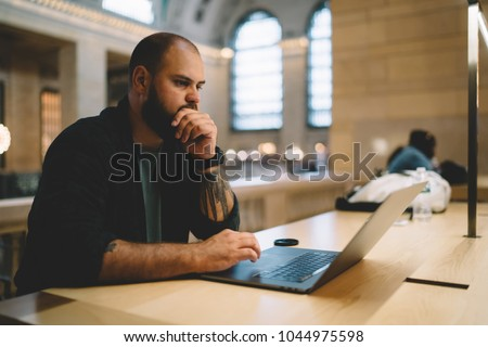 Pensive male student sitting in university library with laptop computer preparing for examinations,thoughtful hipster guy studying online via netbook and wifi connection concentrated on autodidact